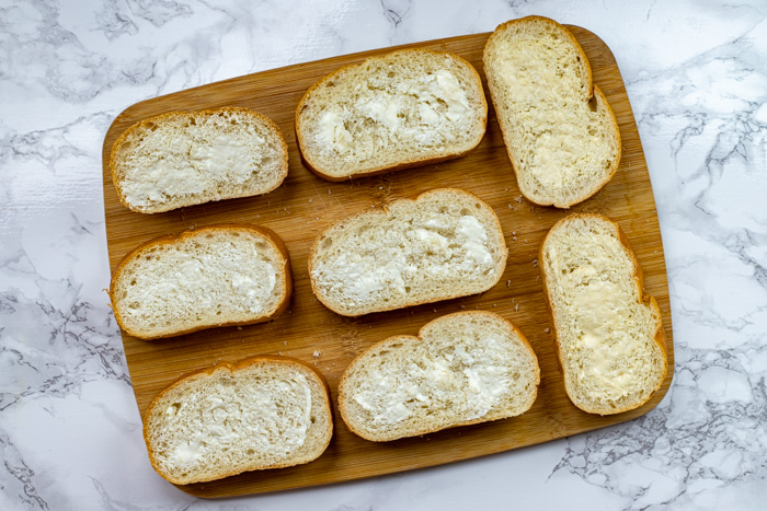 Sliced bread covered with butter on a bamboo tray on a white and grey marbled surface
