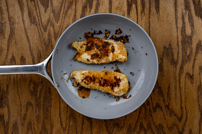 Cooked chicken in a skillet on a wooden surface