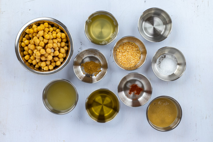 Ingredients for garlic hummus in stainless steel bowls on a white surface