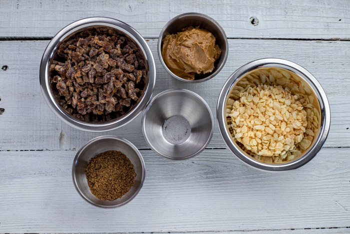 Ingredients for almond-date energy balls in stainless steel bowls on a white wooden surface