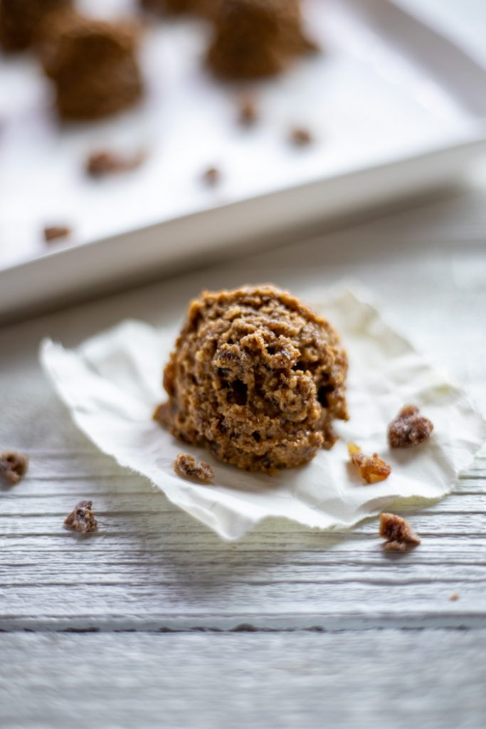 Almond-Date energy ball on a piece of parchment paper with a tray of energy balls behind all on a white wooden surface (vertical)