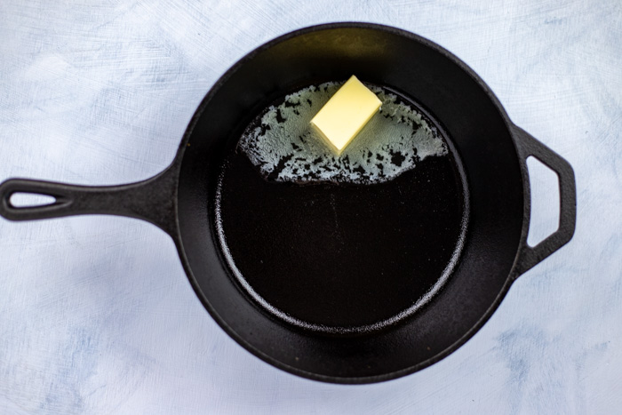 Butter melting in a cast-iron pan on a white and blue surface