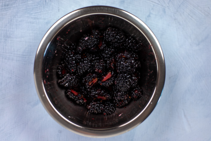 Sliced blackberries in a stainless steel bowl on a white and blue surface