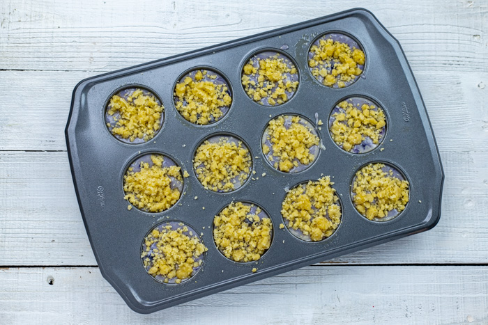 Blueberry muffins with cornmeal streusel topping in a muffin pan on a white wooden surface