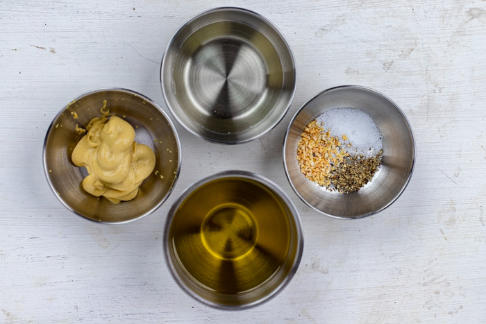Ingredients for dijon vinaigrette dressing in stainless steel bowls on a white and grey surface