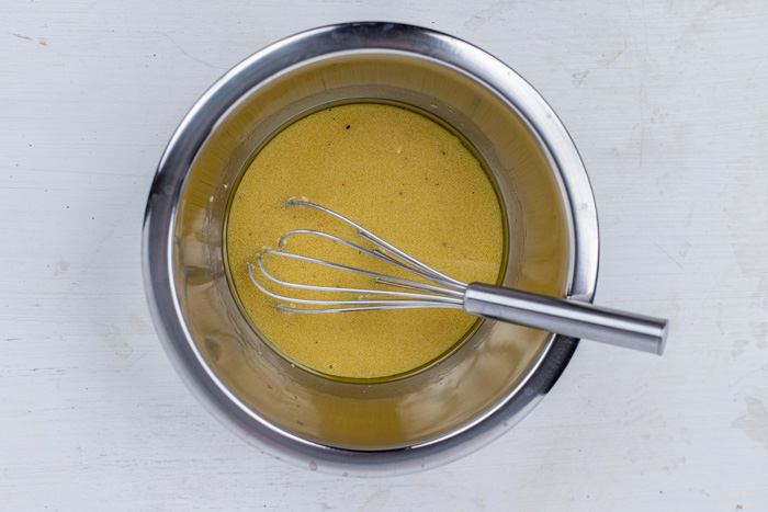 Wire whisk with dijon dressing in a stainless steel bowl on a white and grey surface
