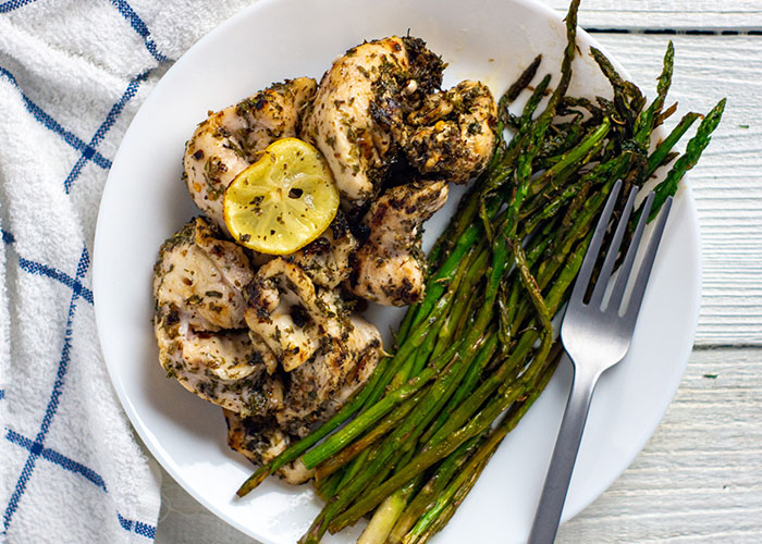 Lemon-herb chicken kabobs next to cooked asparagus with a stainless steel fork on a round white plate with a white and blue towel behind all on a white wooden surface