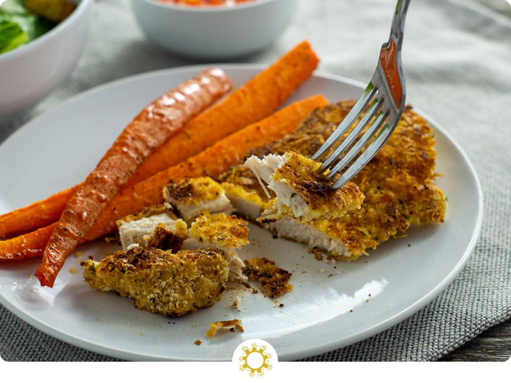 Sliced parmesan-crusted chicken with carrots on a round white plate with a round white bowl of balsamic ketchup behind and a white towel all on a wooden surface (with logo overlay)