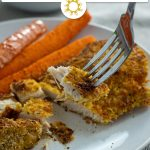 Sliced parmesan-crusted chicken with carrots on a round white plate with a round white bowl of balsamic ketchup behind and a white towel all on a wooden surface (with title overlay)