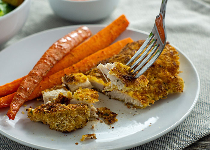 Sliced parmesan-crusted chicken with carrots on a round white plate with a round white bowl of balsamic ketchup behind and a white towel all on a wooden surface