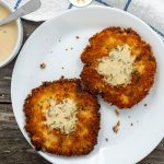 Two salmon cakes topped with buttermilk sauce on a round white plate with a bowl of buttermilk sauce and a white and blue towel behind all on a wooden surface (with title overlay)
