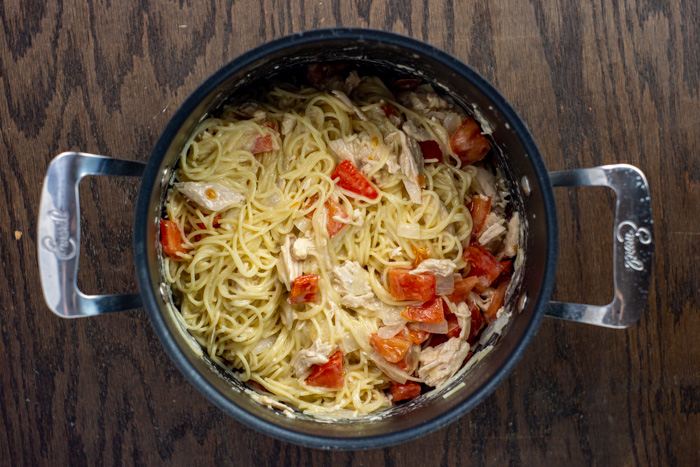 Cooked veggies, spaghetti, and chicken in a stockpot on a wooden surface
