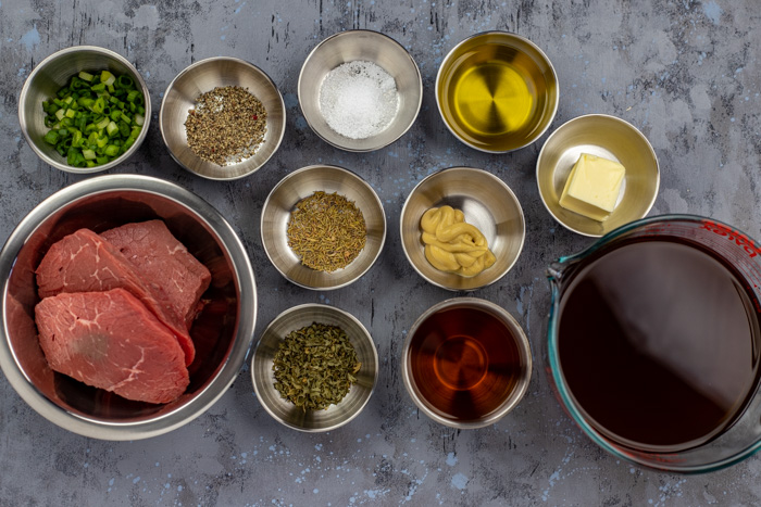 Ingredients for sirloin steak with dijon sauce in stainless steel bowls on a grey and blue surface