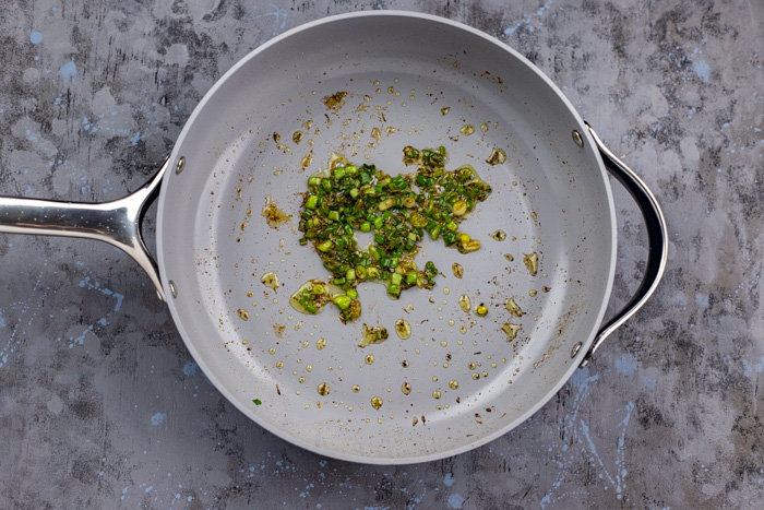 Green onion and seasonings in a skillet on a grey and blue surface