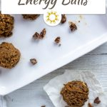 Almond-Date energy ball on a piece of parchment paper with a tray of energy balls behind all on a white wooden surface (with title overlay)
