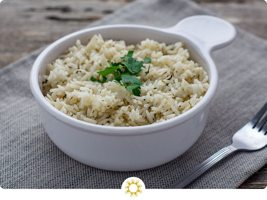 Herbed rice in a round whtie bowl with a grey placemat and stainless steel fork on a wooden surface (with logo overlay)