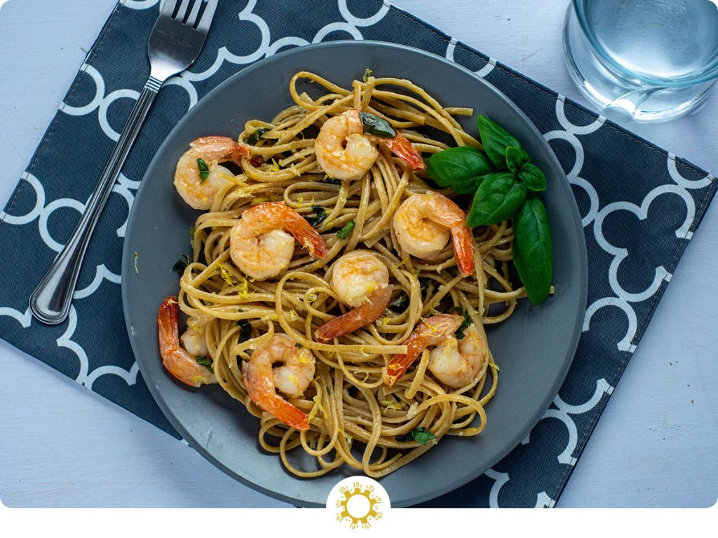 Shrimp scampi with basil on a round gray plate on top of a grey and white placemat with a stainless steel fork and a glass of water all on a white surface (with logo overlay)