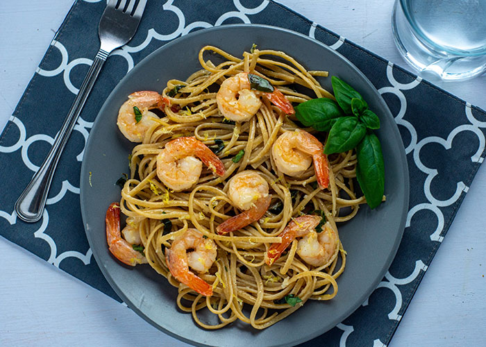 Shrimp scampi with basil on a round gray plate on top of a grey and white placemat with a stainless steel fork and a glass of water all on a white surface