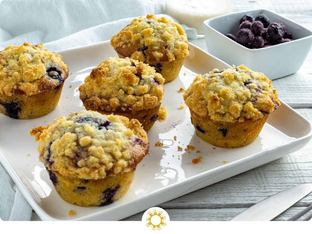 5 blueberry muffins with cornmeal streusel on a square white plate with a stainless steel fork and knife in front and a white square bowl of blueberries and a glass of milk behind next to a white towel all on a white wooden surface (with logo overlay)