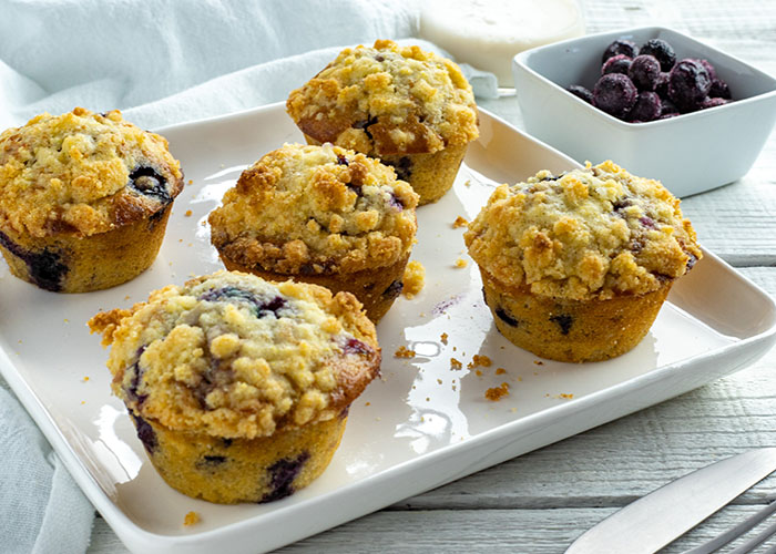 5 blueberry muffins with cornmeal streusel on a square white plate with a stainless steel fork and knife in front and a white square bowl of blueberries and a glass of milk behind next to a white towel all on a white wooden surface