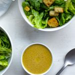 Dijon vinaigrette dressing in a small round white bowl next to two round white bowls of salad, a stainless steel spoon, and a white towel all on a white and grey surface (with title overlay)