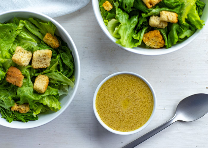 Dijon vinaigrette dressing in a small round white bowl next to two round white bowls of salad, a stainless steel spoon, and a white towel all on a white and grey surface